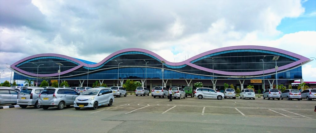Parking area of Domine Eduard Osok Airport Sorong with unique airport building in the background