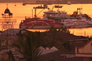View of the harbour of Sorong during sunset with mosque, ferries and boats