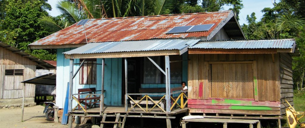 Colorful house with solar panels and little kid on the terrace