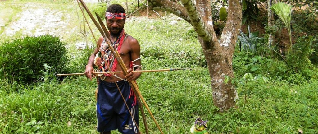 Head of the village poses with colorful necklaces and traditional spear