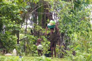 Two kids preparing to wash dishes at a river in West Papua