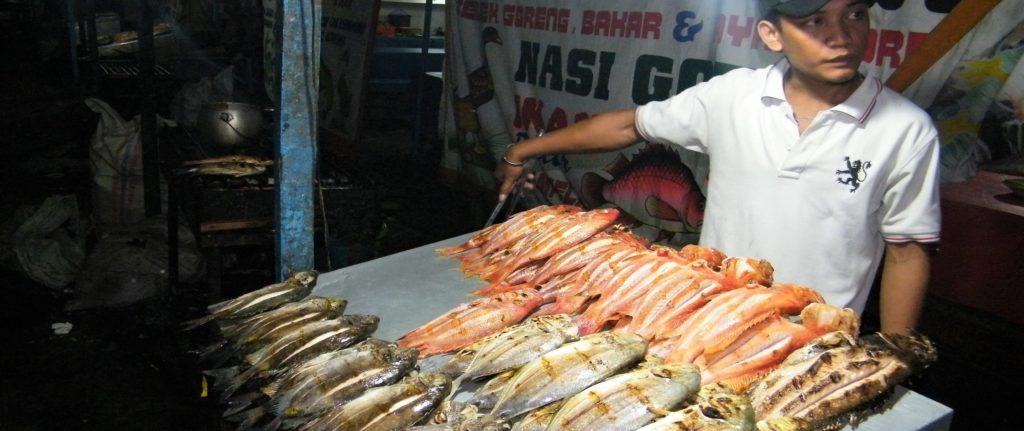 Young man selling grilled fish at Tembok Berlin