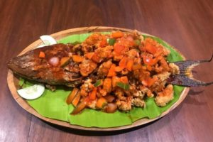 Big plate of whole fried fish with tomatoes and veggies
