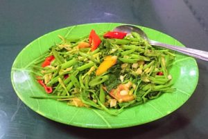 A plate of water spinach with papaya flowers