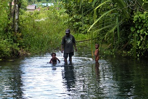 Papuan man with two kids in a river in West Papua