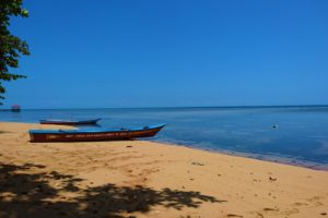 Two wooden boats on a beach with flat sea