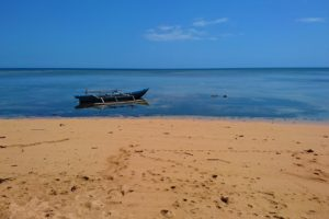 Wooden boat floating in the water at a beach